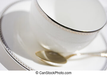 White cup with saucer and teaspoon