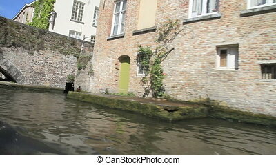 sailing over canal with vintage houses and bridge in Brugge,...