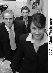 business team - three business people looking towards camera...