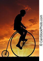 silhouette cyclist on historic bicycle in the sunset