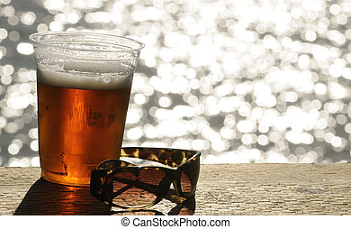 Summer refreshment - Glass of beer and a pair of sunglassas...