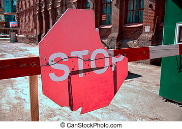 A red stop sign on a barrier