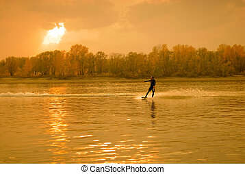 The sportsman on a water ski in the autumn