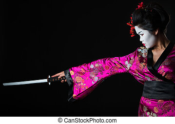 Portrait of geisha warrior with sword isolated on black