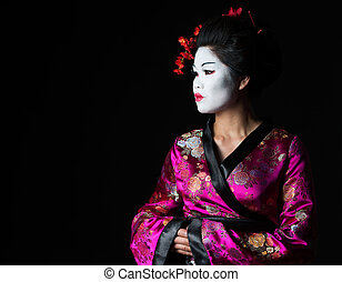 Portrait of geisha looking on copy space isolated on black