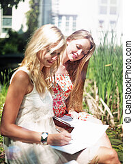 Study outdoors - two gilrs are learning outside in the park