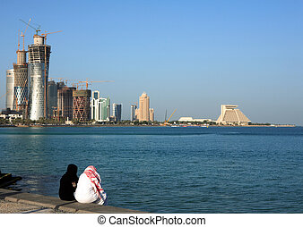 Qatari couple on Doha Corniche - A Qatari man and woman...
