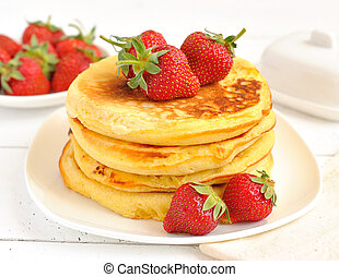 Pancakes with strawberries on a white table