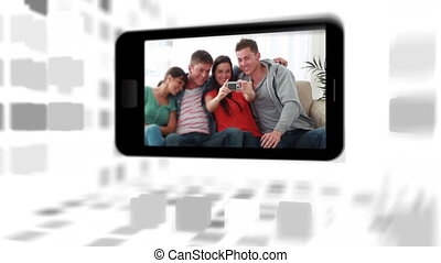 Videos of a family in living room on a smartphone screen...