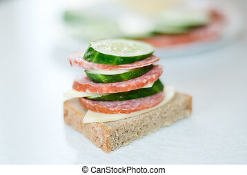 Sandwich with sausage, cheese and a cucumber.