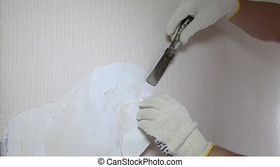 Man removing old wallpaper with the tool, timelapse
