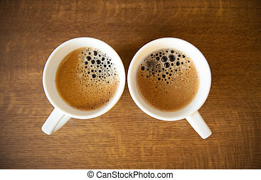 Two whte cups with espresso on wood table