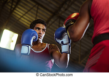 Two male athletes fight in boxing ring - Sport and people,...
