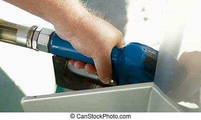 Fuel Pump - Close-up of a mans hand using a petrol pump to...