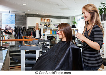 Hair Dresser with Customer in Beauty Salon - Young female...