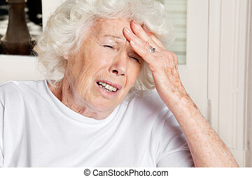 Woman With Headache - Senior woman with eyes closed...