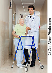 Doctor Assisting An Old Woman With Her Walker - Full length...