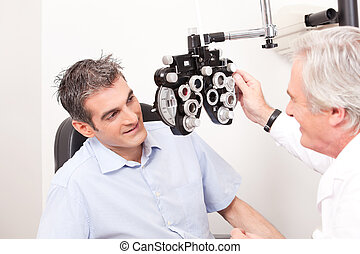 Optometrist doing Sight Testing - Optometrist doing sight...