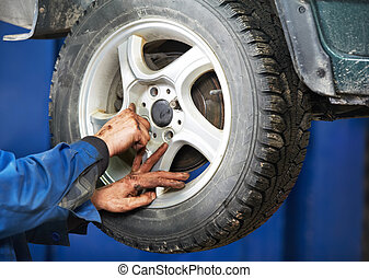mechanic installing car wheel at service station - mechanic...