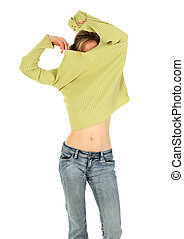 Woman in jeans takes off a green sweater - Young woman in...