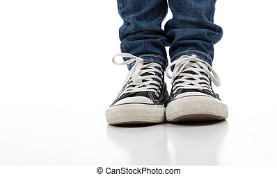 Vintage, antique athletic shoes on a white background with jeans