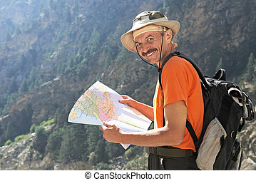 Tourist hiker with map in mountains - One smiling happy...