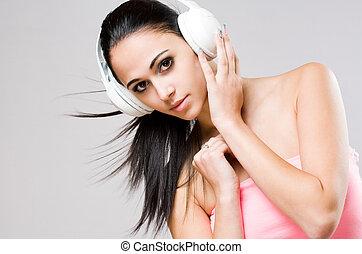 Brunette beauty wearing white headphones.