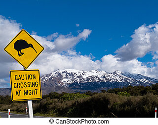 Kiwi Crossing road sign and volcano Ruapehu in NZ - New...