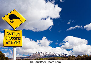 Kiwi Crossing road sign and volcano Ruapehu NZ - New Zealand...