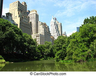 Skyscrapers of Manhattan from Central Park with Lake and...