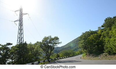 power line tower near a mountain road. Passing motor...