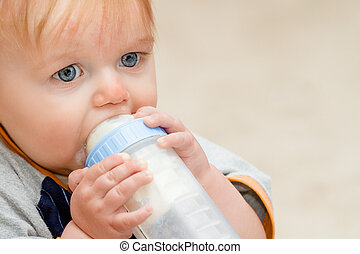 Young toddler boy drinking bottle