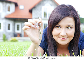 woman holding keys with house background