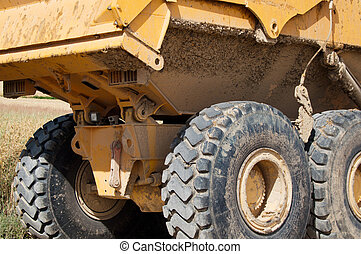 Mining Truck - Large yellow mining truck with huge tires at...