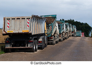 Dump Trucks - Row of Dump Trucks and Earth Moving Equipment...