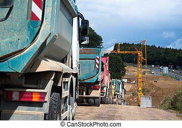 Highway Construction - Row of dum trucks being parked at a...