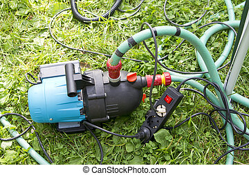 Garden hose and water pump connection in the garden