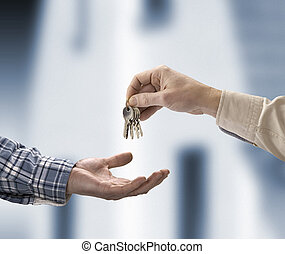 Man is handing a house key to a other man in the shape of...