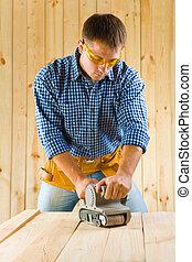 men works with detail sander