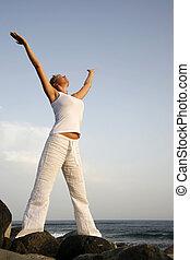 Dawn Meditation - Woman meditating by the sea at dawn