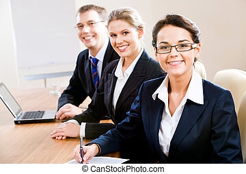 Business group - Group of three business people looking at...