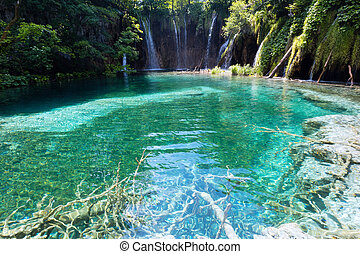 Beautiful lake with clear sea-green water and waterfall behind (Plitvice Lakes National Park, Croatia)