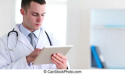 Doctor using a tactile tablet at hospital