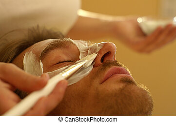 Male Facemask - A man receives a facemask treatment in the...
