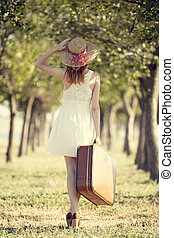 Redhead girl with suitcase at trees alley