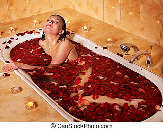 Woman relaxing in bath - Woman relaxing in bath with rose...