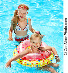 Children in swimming pool - Children sitting on inflatable...