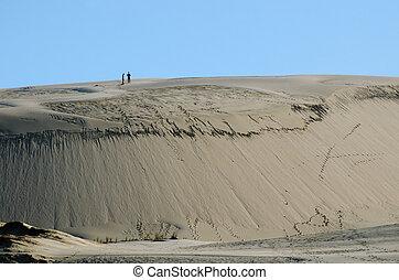 Te Paki Sand Dunes - Two people on Te Paki sand dunes in...