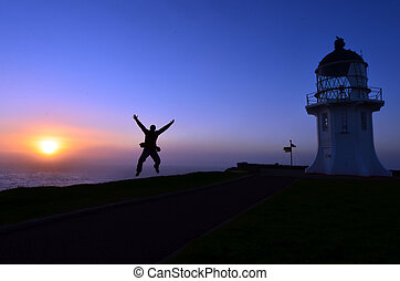 Cape Reinga Lighthouse - A man jumps in the air during...