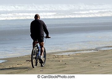 Ninety Mile Beach - A man rides a bike over Ninety Mile...